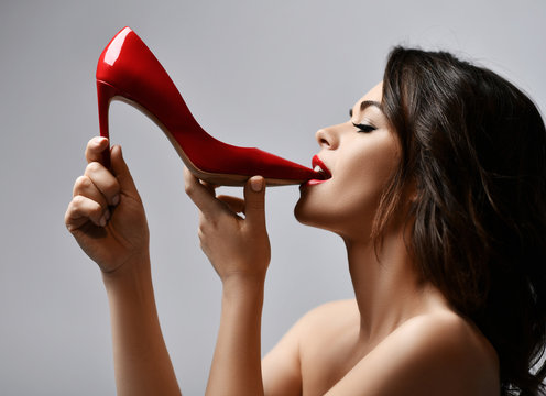 Portrait of young beautiful sexy brunette woman with red lips biting red shiny shoe with high heel over light grey background