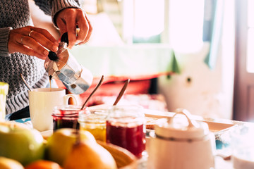 Close up of woman caucasian hands serving and doing traditional coffee dor breakfast  morning time - bright image with food and drinks at home