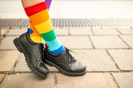 female legs in lgbt rainbow socks wearing male boots.