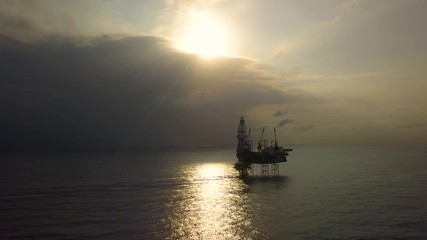 Wall Mural - Aerial view of the jack up rig shot during sunset time. Fly around the jack up rig with a drone.