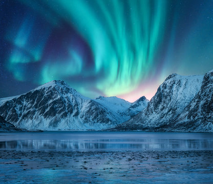 Aurora borealis over the snowy mountains, coast of the lake and reflection in water. Northern lights above snow covered rocks. Winter landscape with polar lights, fjord. Starry sky with bright aurora