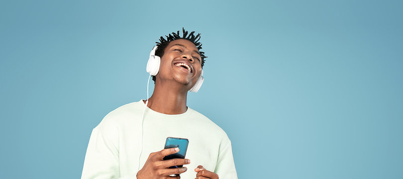Happy african man listening to music.