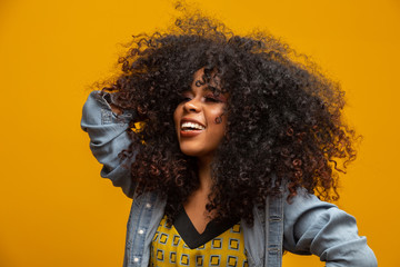 Beauty portrait of african american woman with afro hairstyle and glamour makeup. Brazilian woman. Mixed race. Curly hair. Hair style. Yellow background.