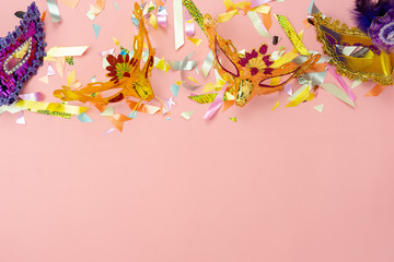 Table top view aerial image of beautiful colorful carnival festival background.Flat lay accessory object the several mask & decor confetti on modern pink paper at home office desk studio.copy space.