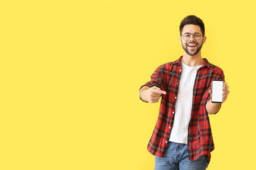 Happy young man with mobile phone on color background Wall mural