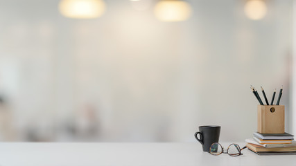 Close up view of workspace with stationery, glasses and coffee cup on white table with blurred background