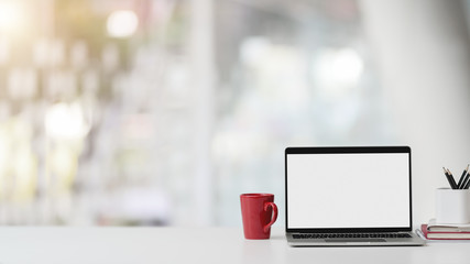 Wall Mural - Closeup view of office room with blank screen laptop, stationery, coffee cup and copy space on white table