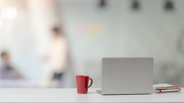 Close up view of workspace with laptop, notebooks, red coffee cup and copy space on white desk