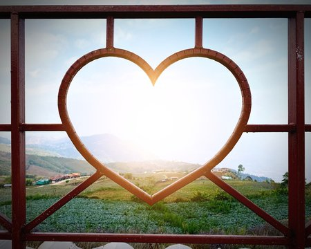 Wrought iron balcony on the roof of the house or resort, bent to a transparent heart shape, looking through a beautiful complex and green of mountain with the morning sunrise, fresh air and good view