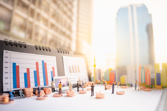 Miniature people: business man standing with stack of coins, lap top, bar graph on blurred city scape and copy space using as background business money investment plan, real estate, property concept.