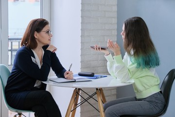 Social worker talking to teenage girl. Psychological assistance in adolescence