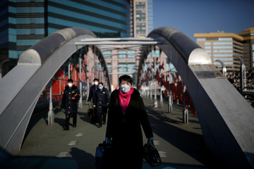 A woman wearing a face mask carries her luggage at a footbridge near Beijing Railway Station as the country is hit by an outbreak of the new coronavirus, in Beijing
