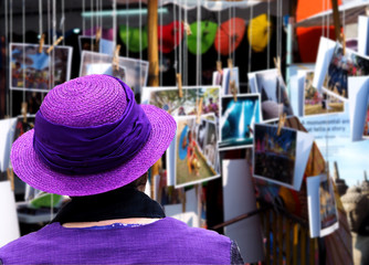 A woman in a purple dress looking postcard hanging show .