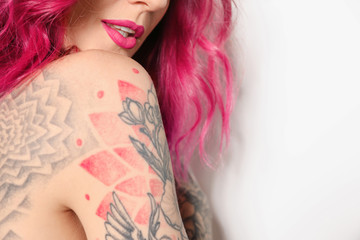 Beautiful woman with tattoos on body against white background, closeup