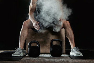 Strong man applying magnesium powder on hands before training with kettlebells in gym, closeup