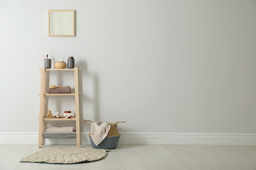 Wooden shelving unit with toiletries near white wall indoors, space for text. Bathroom interior element