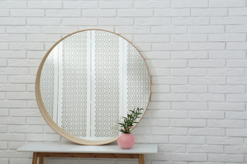 Round mirror and green plant near white brick wall