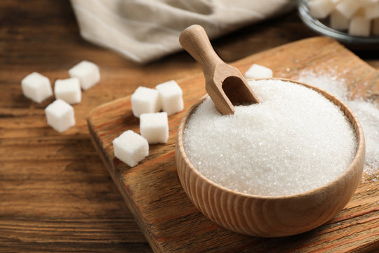 Granulated sugar in bowl on wooden table