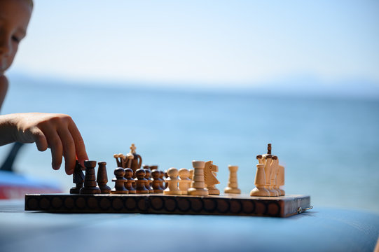 Little boy playing chess on the beach
