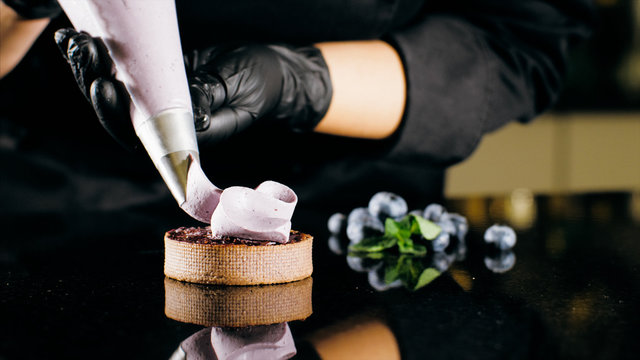 Pastry chef decorates biscuit with purple cream from pastry bag, close-up. Preparation of blueberry cake at commercial bakery with piping bag
