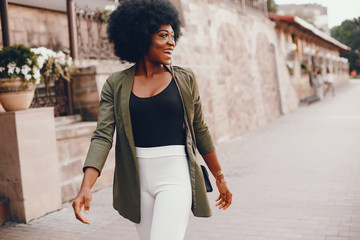 Fashionable girl in a summer city. Black lady in a green jacket Wall mural
