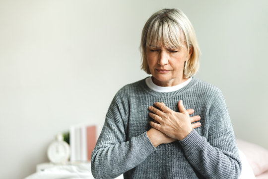 Senior adult elderly women sit on bed with chest pain suffering from heart attack in the bedroom.Healthcare and medical concept
