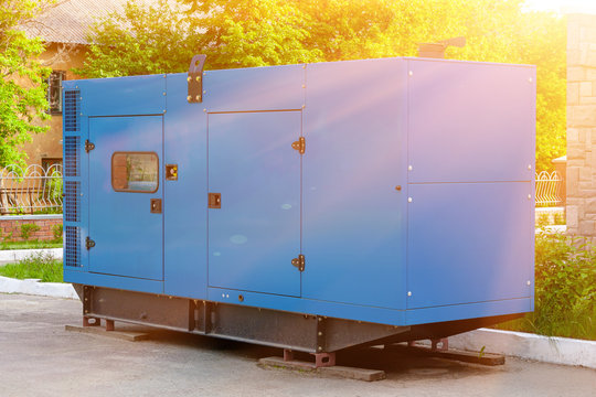 Diesel generator for emergency power supply at the wall of a medical center against the backdrop of green trees in fine sunny weather.