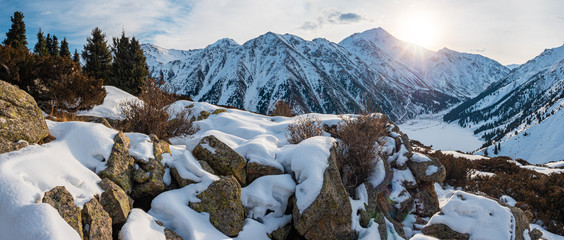 Panorama of sunrise over a mountain lake in winter