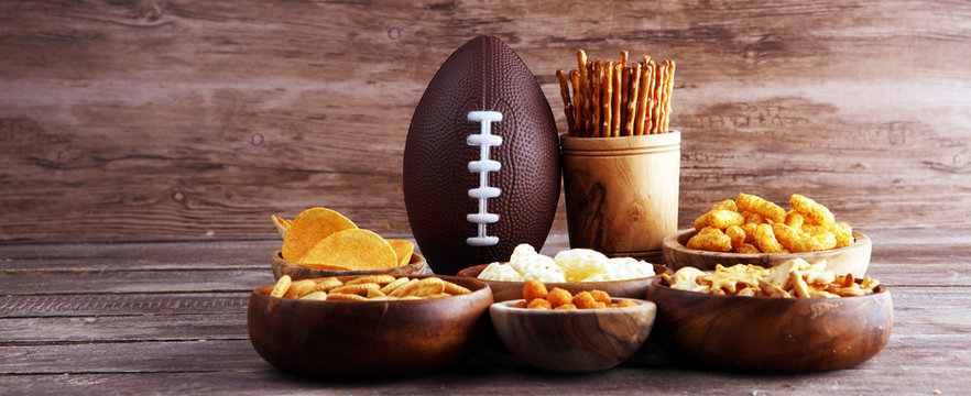 Chips, salty snacks, football on a table. Great for Bowl Game snack projects.