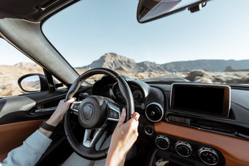 Woman driving car on the desert road, close-up view focused on the steering wheel and hands....