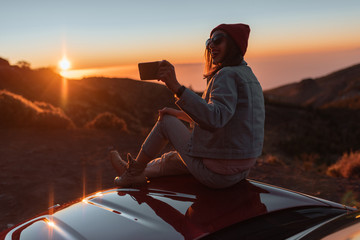 Fotorollo Schokobraun Young woman photographing with phone beautiful landscape during a sunset, sitting on the car hood while traveling high in the mountains