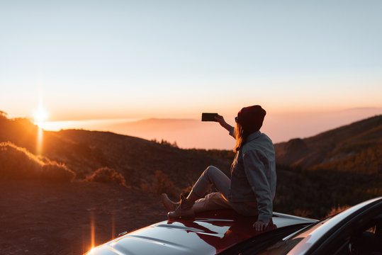 Young woman photographing with phone beautiful landscape during a sunset, sitting on the car hood while traveling high in the mountains