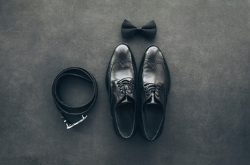 Stylish black lacquered men's shoes, leather belt and bow tie on vintage dark grey background. Men's accessories. Groom set. Top view, copy space. Wall mural