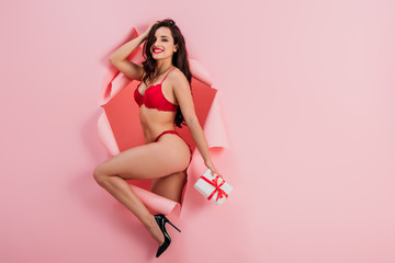 sexy girl in red lingerie holding gift box and smiling at camera while standing in paper hole on pink background