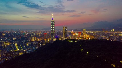 Wall Mural - Hyperlapse or Dronelapse Aerial view of Business district in city of Taipei, Taiwan at sunset