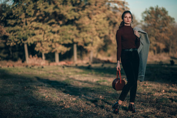 Young fashionable beautiful girl in a black jeans and with a dark red bag. Portrait shooting of a stylish girl. Facial shooting, street style and fashion. Professional model.