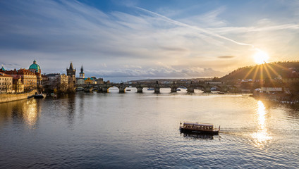 Prague, Czech Republic - Panoramic view of the world famous Charles Bridge (Karluv most) on a sunny winter afternoon with sightseeing boat, blue sky and sunlight