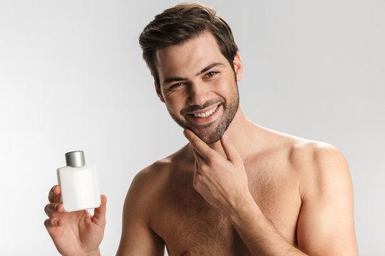 Photo of joyful half-naked man smiling and showing lotion