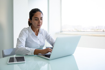 Serious young businesswoman using laptop in office. Focused young businesswoman sitting at desk and using laptop computer in modern office. Business and technology concept