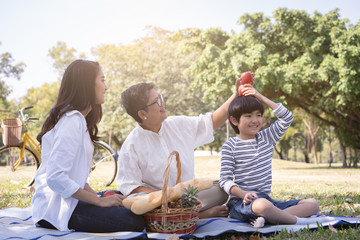 Asian family with son sitting hold apple above his head in the public park. Concept of lifestyle at happy in family holiday