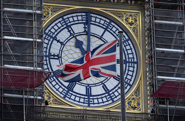 The British union flag is seen fluttering as the clock face of Big Ben shows eleven o'clock, London, Britain