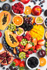 Wall Mural - Healthy raw rainbow fruit platter mango papaya strawberries oranges passion fruits berries on oval serving plate on light concrete background, top view, selective focus