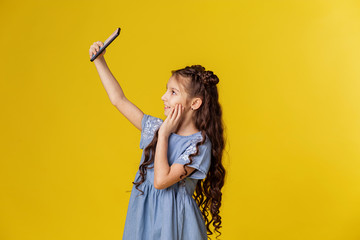 Little girl kid makes selfie on the phone. Children and gadgets. Smartphone technology taking pictures of yourself. Yellow background place for text banner. Parental control