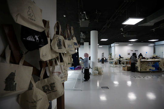Jordanian and Syrian women work in the creation of tote bags as part of the Teeah project, which aims to promote the reduction of plastic bags use, in Irbid
