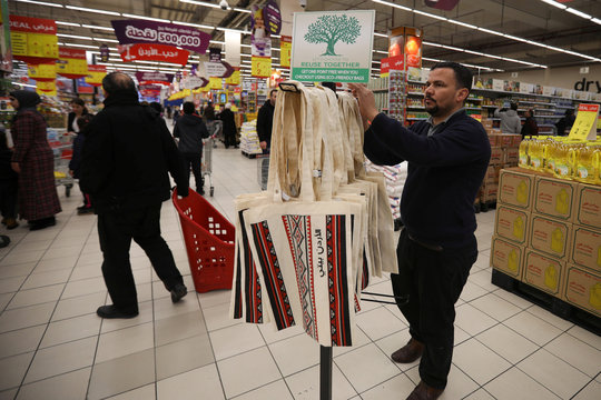 A man stands next to tote bags created by Syrian and Jordanian women as part of the Teeah project, which aims to promote the reduction of plastic bags use, in Irbid
