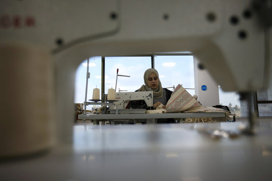A woman works in the creation of tote bags as part of the Teeah project, which aims to promote the reduction of plastic bags use, in Irbid