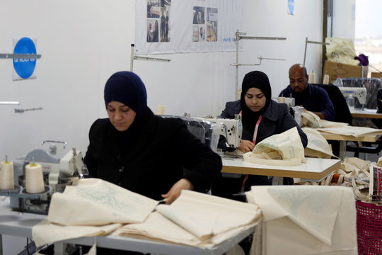 Workers sew tote bags as part of the Teeah project, which aims to promote the reduction of plastic bags use, in Irbid