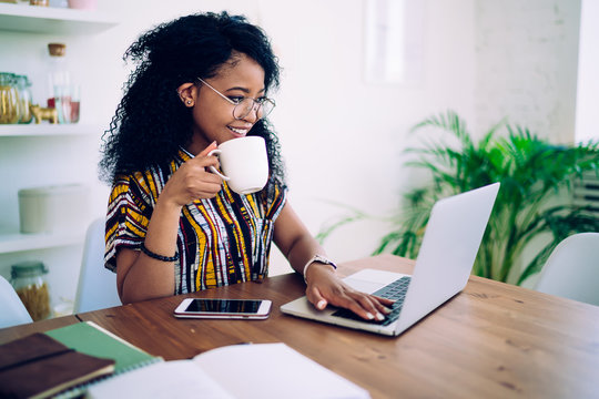 Cheerful young modern woman browsing laptop while drinking coffee at home