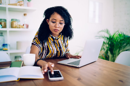 Thoughtful woman using smartphone and laptop at home