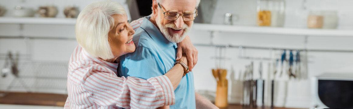Panoramic shot of senior woman hugging smiling husband in kitchen